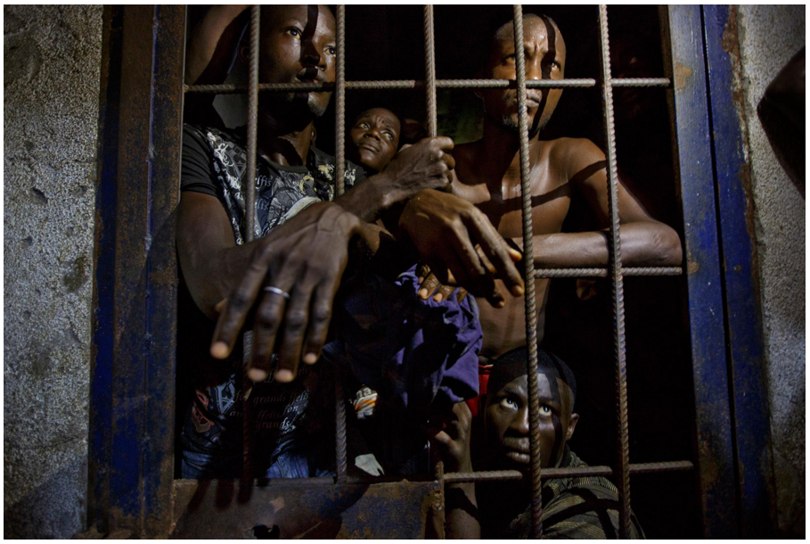 Men wait in a cell inside the police station in Greenville, Sinoe county. Photos by Kuni Takahashi.