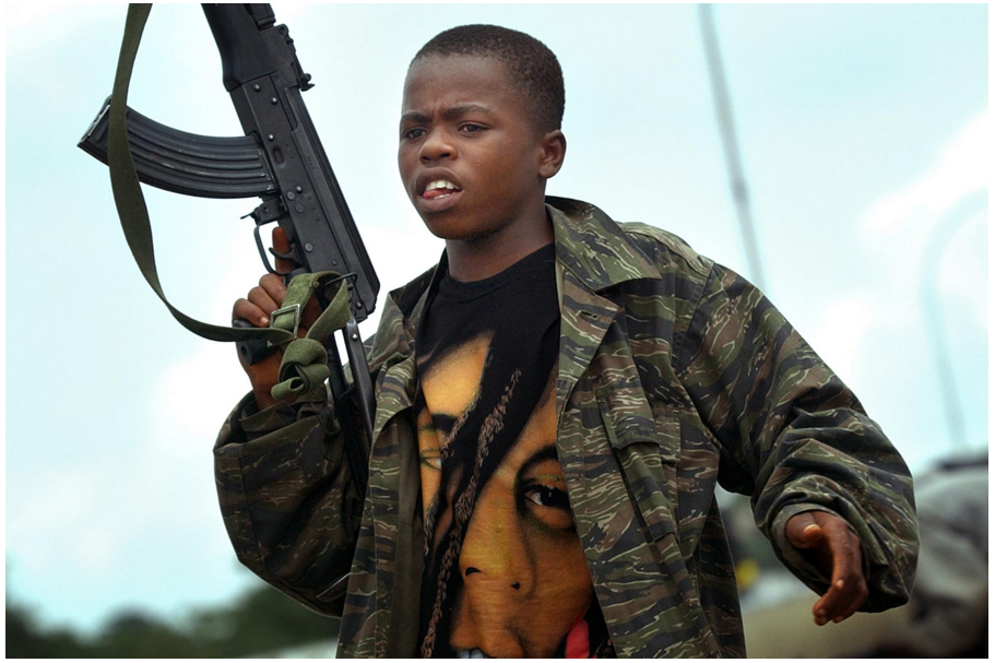Momo Dukoe in 2003, bearing an AK-47. He was 13 years old when photographer Takahashi first encountered him, fighting on the frontline for a militia backed by President Charles Taylor. He had been forcefully recruited when he was 11 years old.