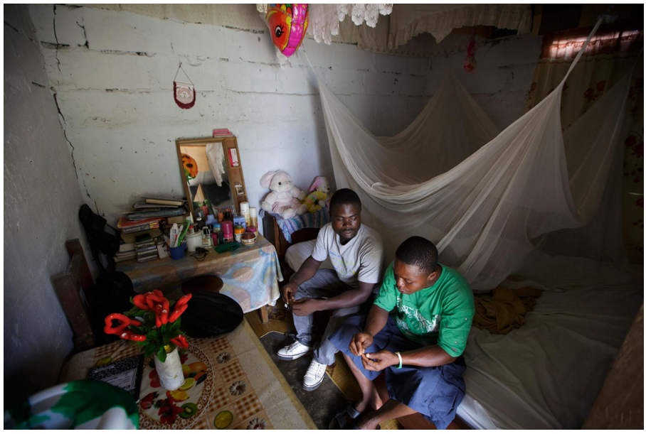 Momo Dukoe, now 25, talks with Daniel in Daniel's room in Monrovia, May 29, 2015.