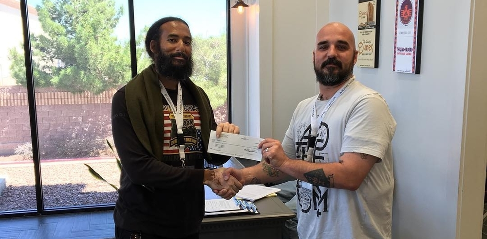 Our store manager Sean Cooper handing over the $1,000 donation to Forgotten Not Gone from our fundraiser with Green Life Productions.