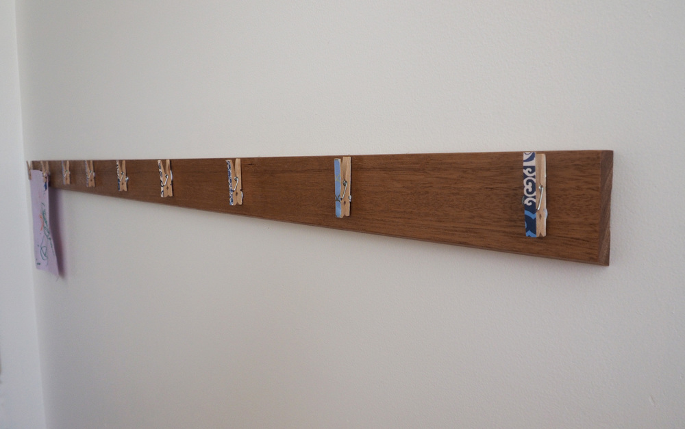 attaching pegs to the art display wall