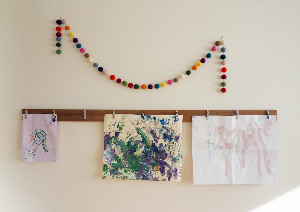A creative way to display artwork with mini-pegs and a simple piece of wood - the perfect way to spruce up a blank wall, while showing off your child's latest masterpieces!