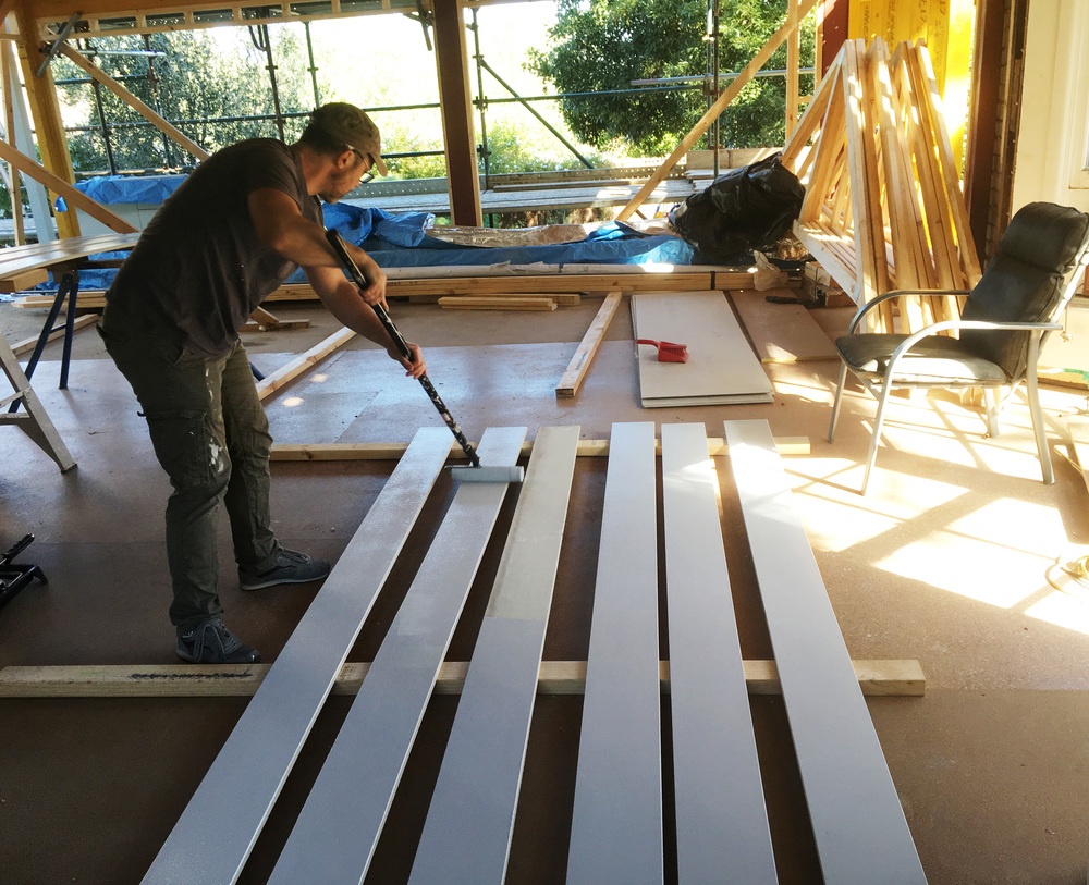Painting the boards with a roller pre-installation