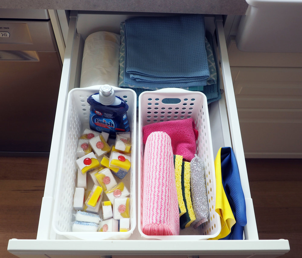 Organise cleaning items in a drawer using plastic baskets to act as dividers