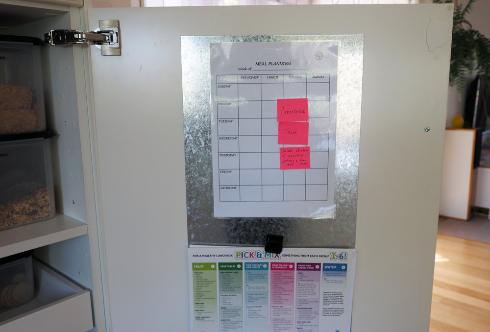 Use the back of the door pantry door to stick metal sheeting or a whiteboard and use it for meal planning or to hold important notes {The Organised You}