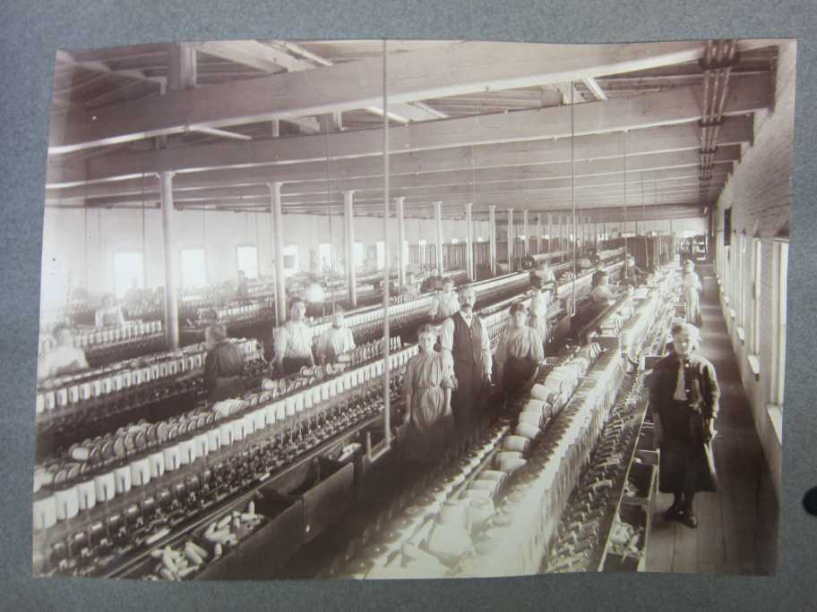 Mill interior photo taken about 1900 and probably similar to Mill 2 (today's Amesbury Industrial Supply) on High St. These machines are spinning frames that produce cotton thread, winding it onto bobbins (spools). The filled bobbins are used in looms that weave fabric on another floor. The young machine attendants remove the full bobbins, while older workers make sure the machines are operating properly. (Photo courtesy of Amesbury Public Library.)