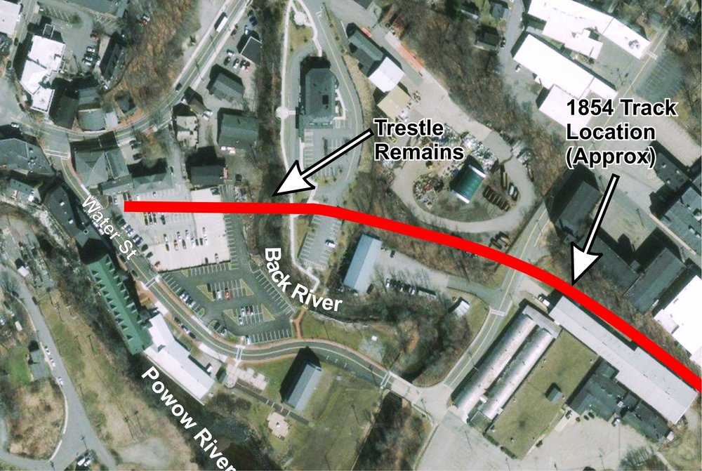 The red line on a current aerial view of the Lower Millyard traces where the tracks ran originally between part of what is now the Riverwalk (the right end) and the former train passenger station (Crave, left end of the red line) [Digital Globe image].