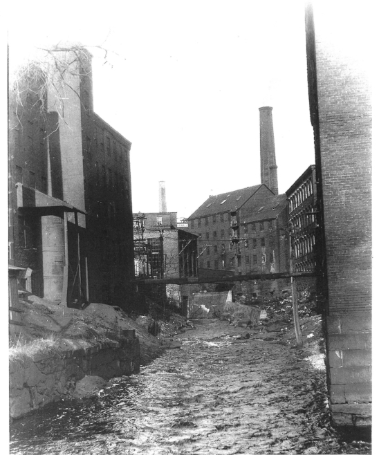 Looking up the Powow River from the lower millyard, about 1920. (Courtesy of Amesbury Public Library.)
