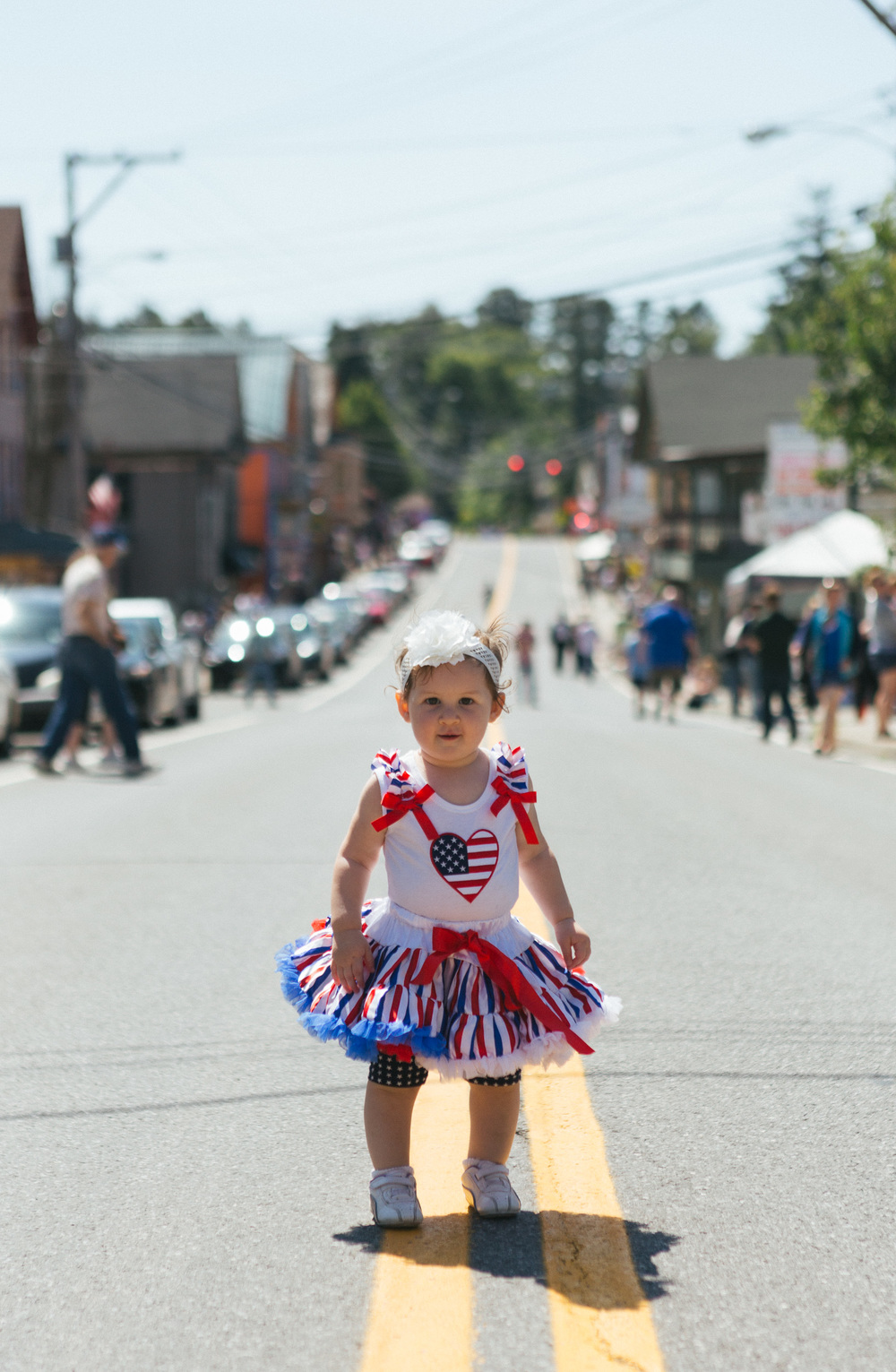 A girl poses for a photo after the road is shut down for the parade.jpg