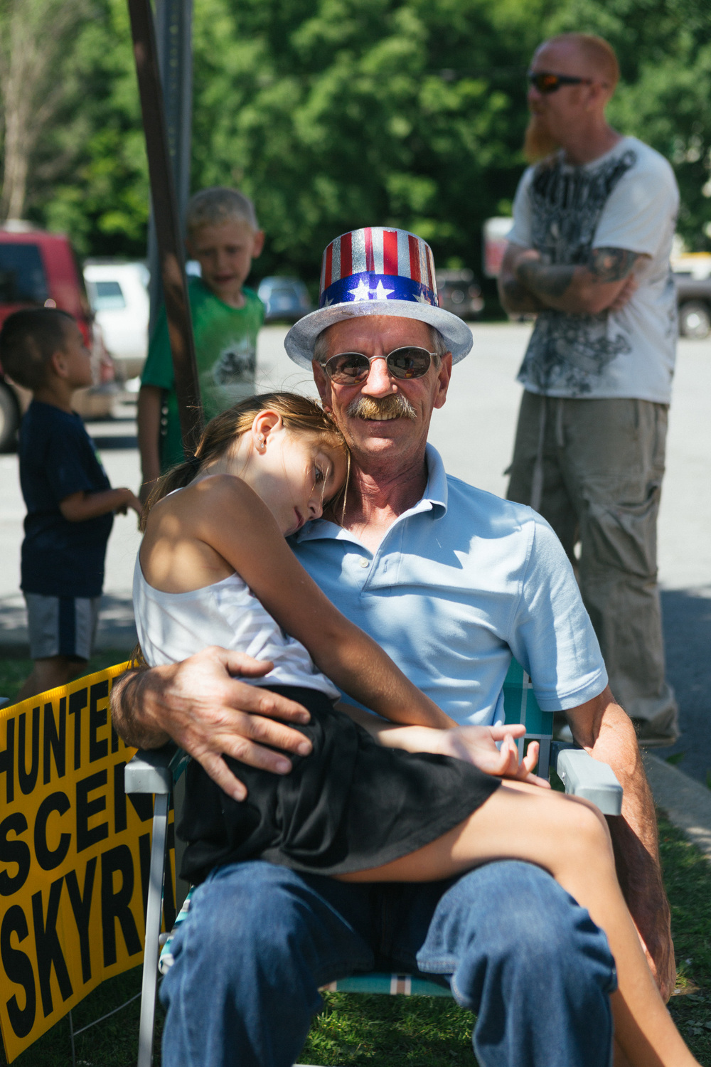 A man holds his granddaughter as they wait for the parade to begin.jpg