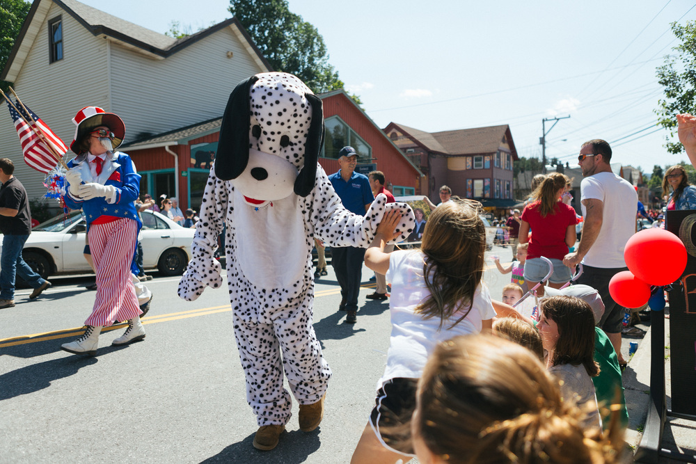 Dalmation mascot gives a high five to children at the Tannersville Parade.jpg