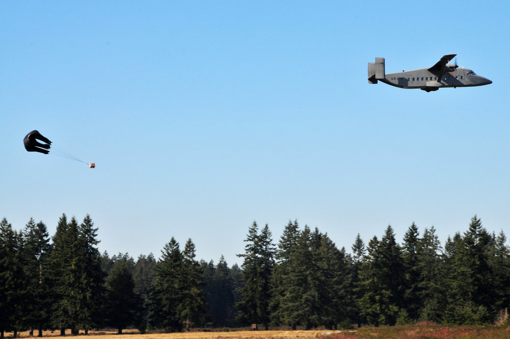 A Sherpa cargo plane drops one of six loads, March 6, during Low Cost Low Altitude (LCLA) drop training by the 593rd Sustainment Brigade. (Photo Credit: Master Sgt. David Largent/ Washington National Guard)      https://www.army.mil/article/18794/fort_lewis_brigade_delivering_supplies_for_less