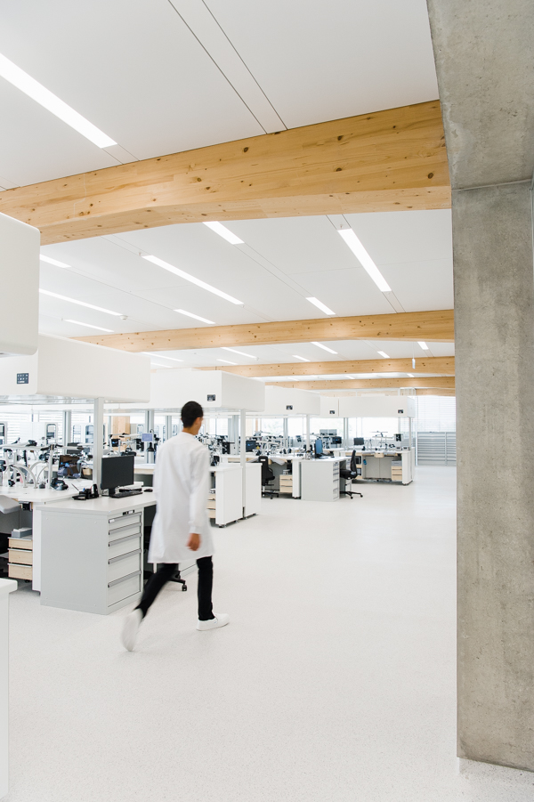 The production spaces at the new Omega building. There is a «Flow box» system installed above every work station, which permits the air to flow from up to down, ensuring a dust free area on the working surface.The tables are custom made for Omega with an ergonomic and adjustable arm-rest with memory foam and an individually adjustable height of the working bench to user size.Every work station has a tablet giving all instructions, making for a paper free work space.There is a scanning system installed in each work station for production traceability on the working surface as well as a key port for working presence/statistics.Each work station is equipped with a USB port for individual music, radio, or podcast listening.