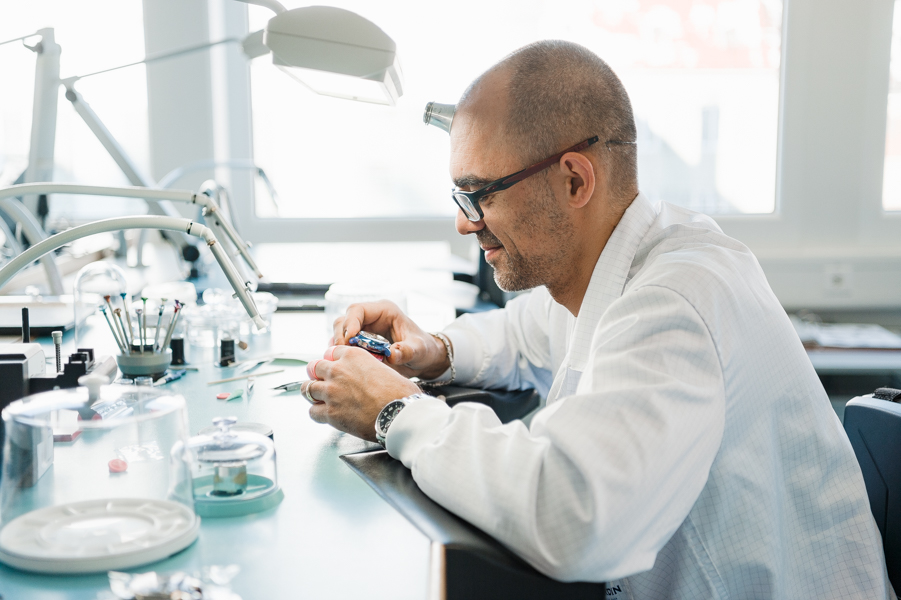 A watchmaker working on assembling a watch. He is checking the movement and listening if it sounds correct.