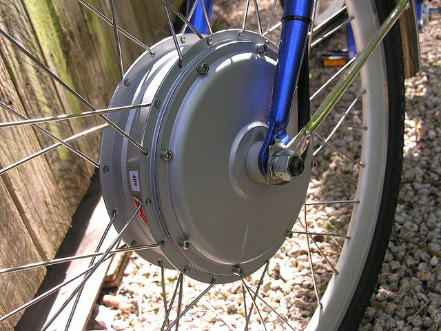 The hub motor is a replacement for the existing wheel hub and includes spokes. The outside of the hub motor spins while the inside is kept fixed to the frame,