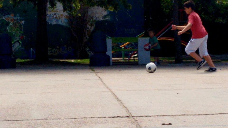 Crianças jogando futebol em uma praça de Montevidéu