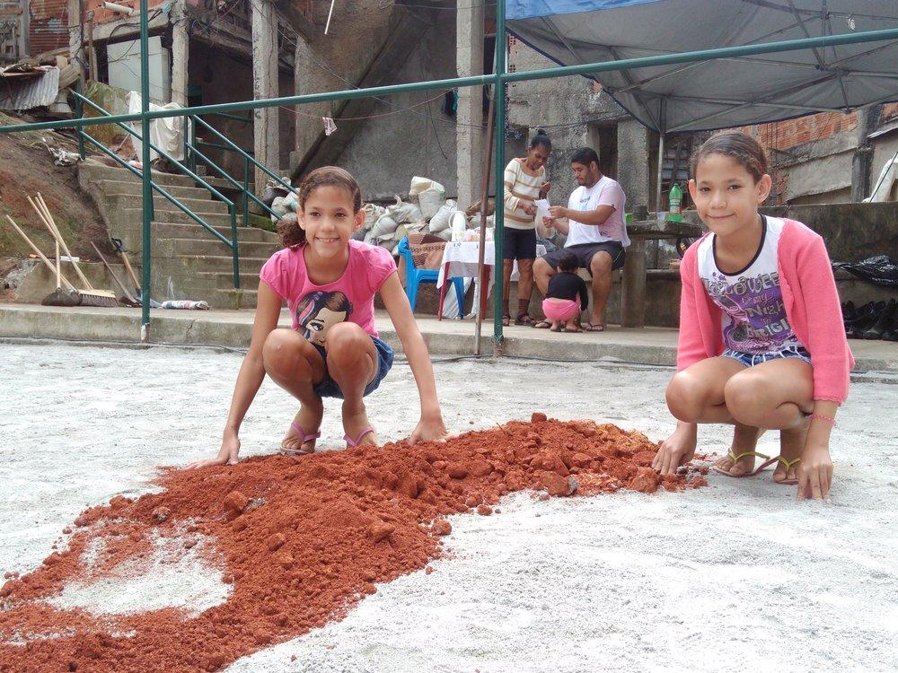 Keciane e Karina em gesto simbólico durante as obras de recuperação do Campo do Tortinho, em 2016.