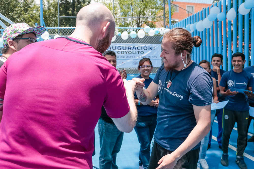 Alfredo comemora com treinador do City in the Community/Cityzens Giving Craig Bell o certificado do Young Leaders Training (Capacitação de Jovens Líderes), realizado no #ProjetoElCoyolito, em agosto de 2017.