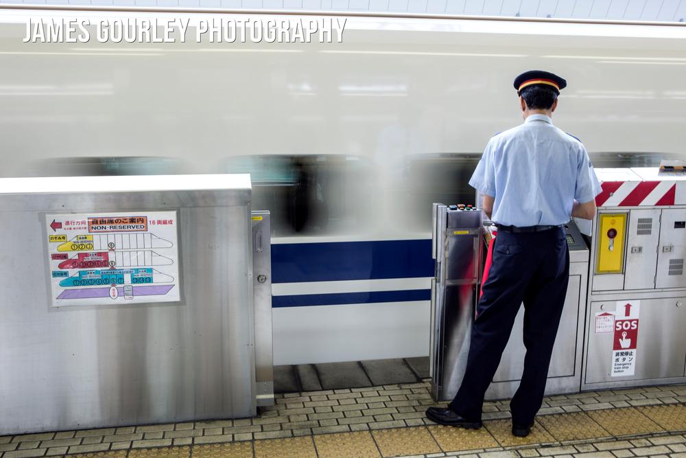 A train guard watches as a Shinkansen Bullet Train leaves Tokyo Station