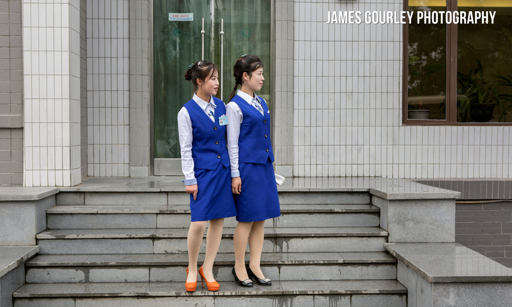Waitresses at a restaurant in Hoeyrong which was opened to non-Koreans for the first time look awkwardly at Western visitors.