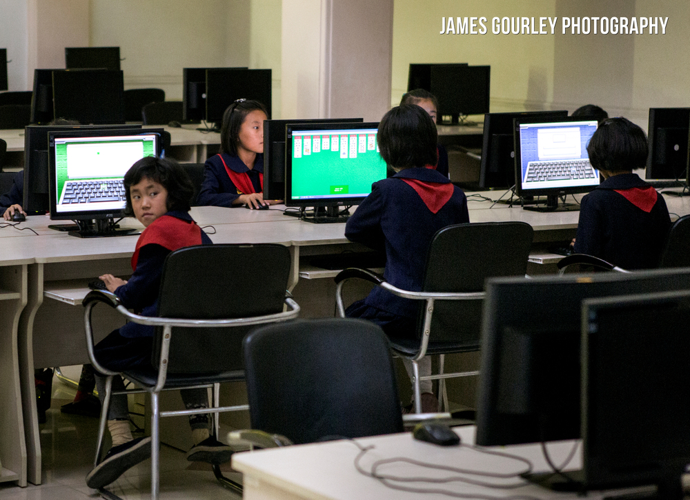 A young student playing Solitaire on a computer at Chongjin Library during a study session