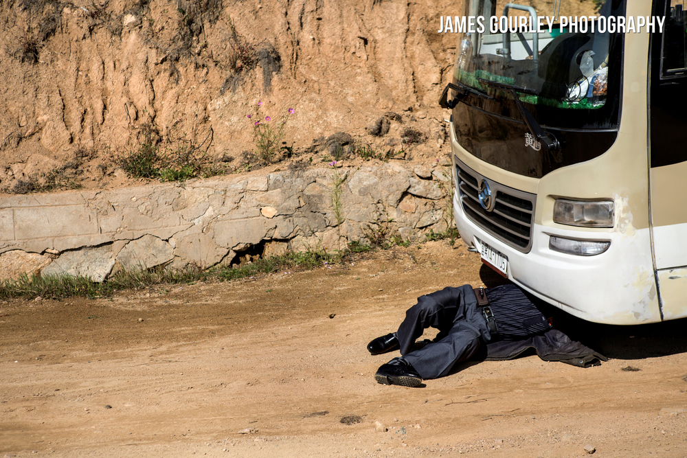 A driver works on his bus on a road towards Gyongsong