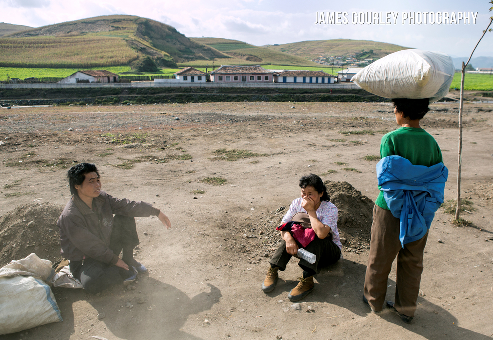 Locals rest at the side of a road, one woman covers her face to avoid dust from passing vehicles.. North Korea only has 724km of paved road, the rest, like most in North Hamgyong, are simple dirt tracks.