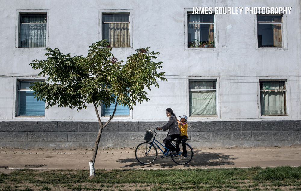A woman and child share a bicycle in the town of Gyongsong. It is a common sight to see two or three people sharing a bicycle as cars and buses are so rare