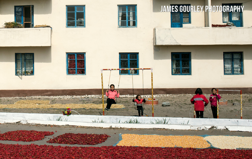 Children play in Hoeyrong City next to a road filled with Chilli Peppers and corn which is dried after harvested. Scenes like this were common as the harvest was under way during my trip.