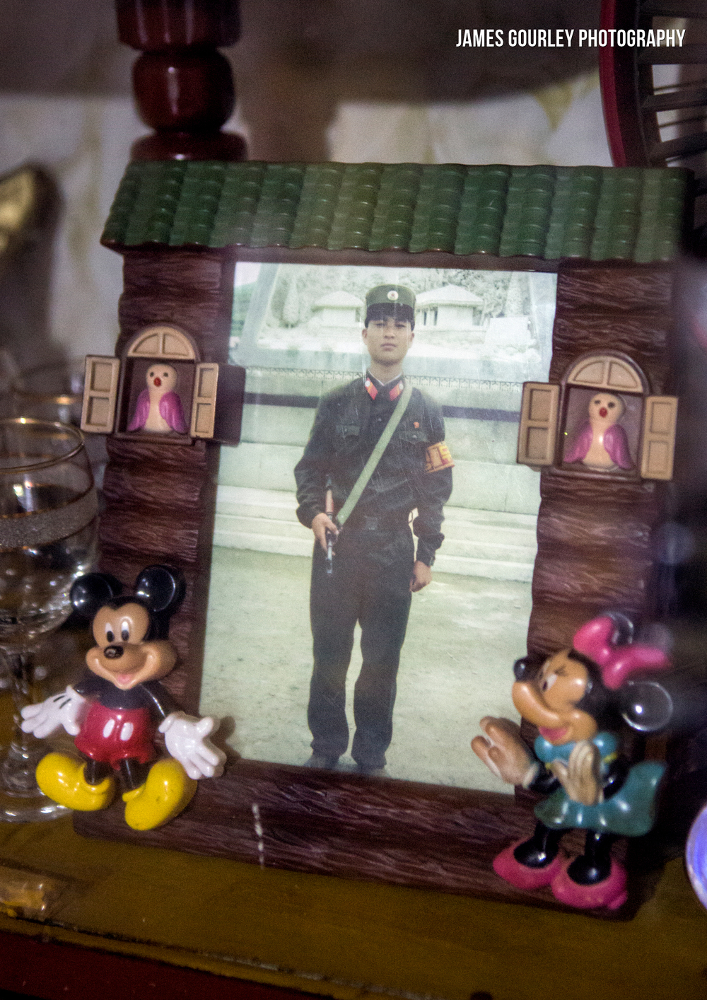 A picture of a North Korean soldier, the son of the home owner is held in a Disney frame in their house in Sea Chilbo