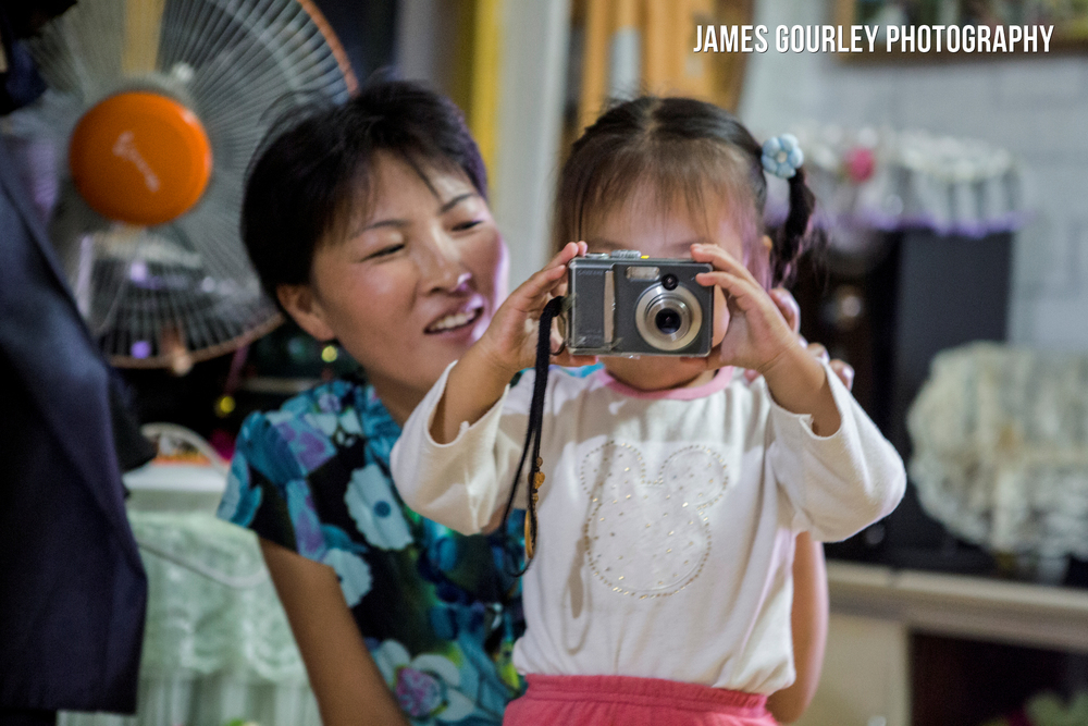 A young girl takes photos whilst her Mother watches on at a Homestay in Sea Chilbo