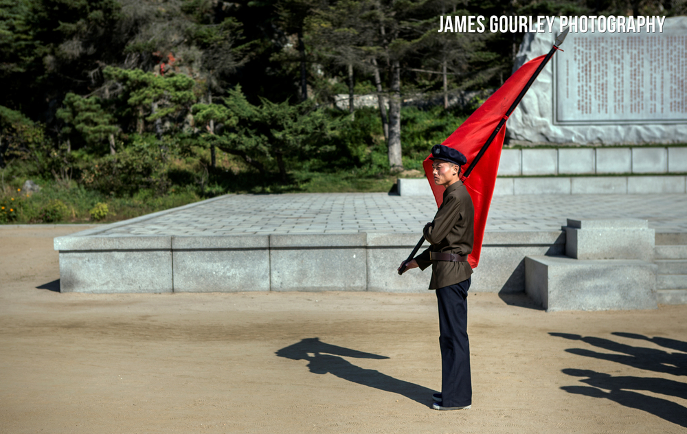 A revolutionary student holds a red flag whilst leading a group of students to a monument
