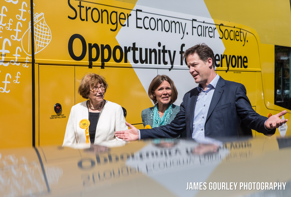 The Deputy Prime Minister and Leader of the Liberal Democrats Nick Clegg walking past the Lib Dem battle bus as he arrives at Topps Nursery in Wimborne today with outgoing MP Annette Brooke (left) and the Lib Dem PPC for Mid Dorset and North Poole Vikki Slade (centre)