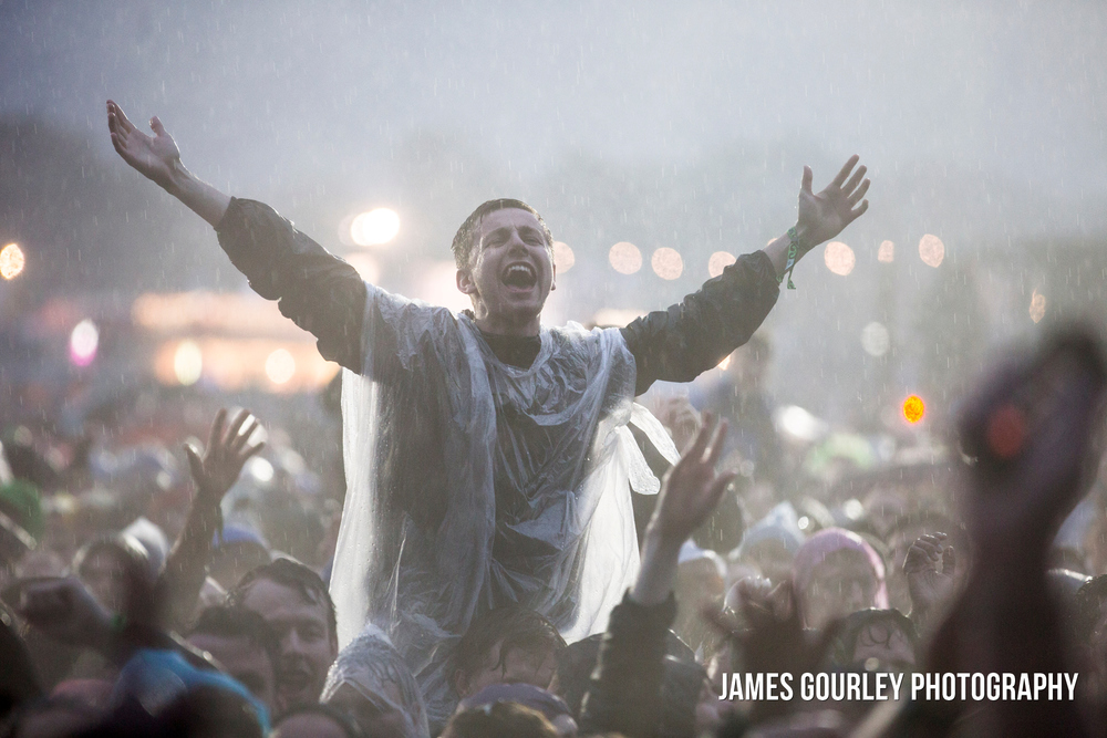 The audience watch The Black Keys performing on the Main Stage at the Isle of Wight Festival 2015 during heavy rain.