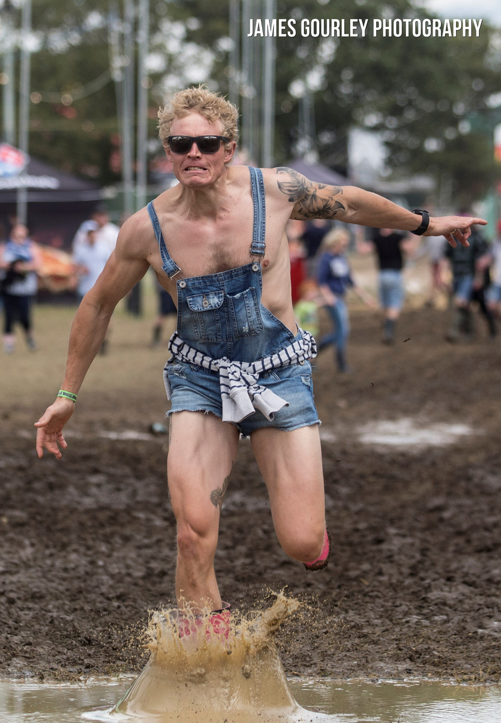 Festival goers struggle with muddy ground after heavy rain at the Isle of Wight Festival 2015