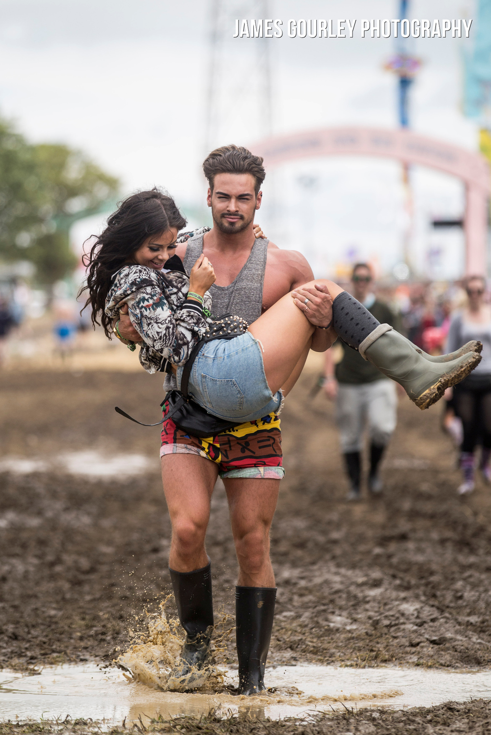 Phillip Sharp carries his girlfriend Becky Collins across muddy ground after heavy rain at the Isle of Wight Festival 2015