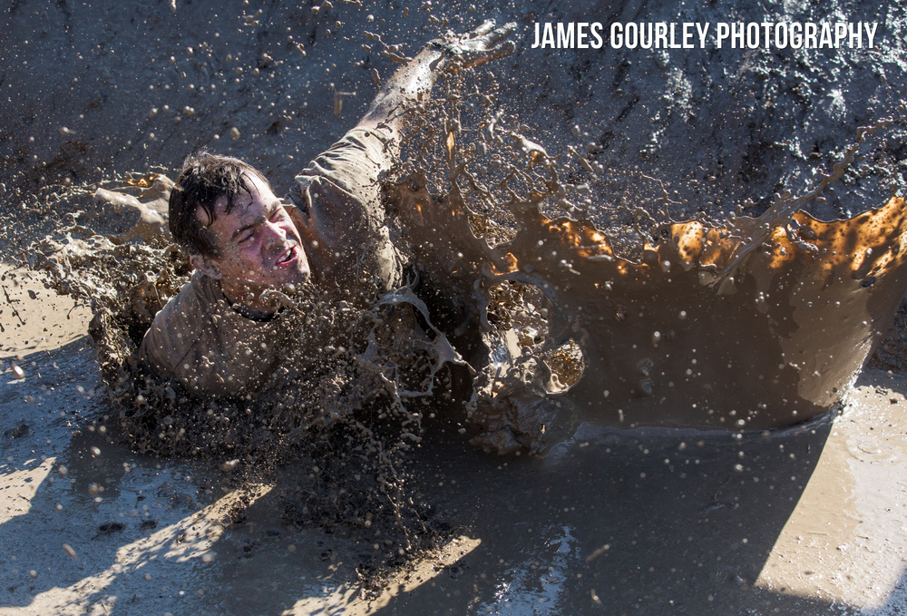 A mud covered participant tackling 'Mud Mile'