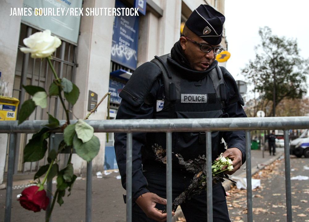 A Police Officer places a white rose in a floral tribute outside the Bataclan Caf�