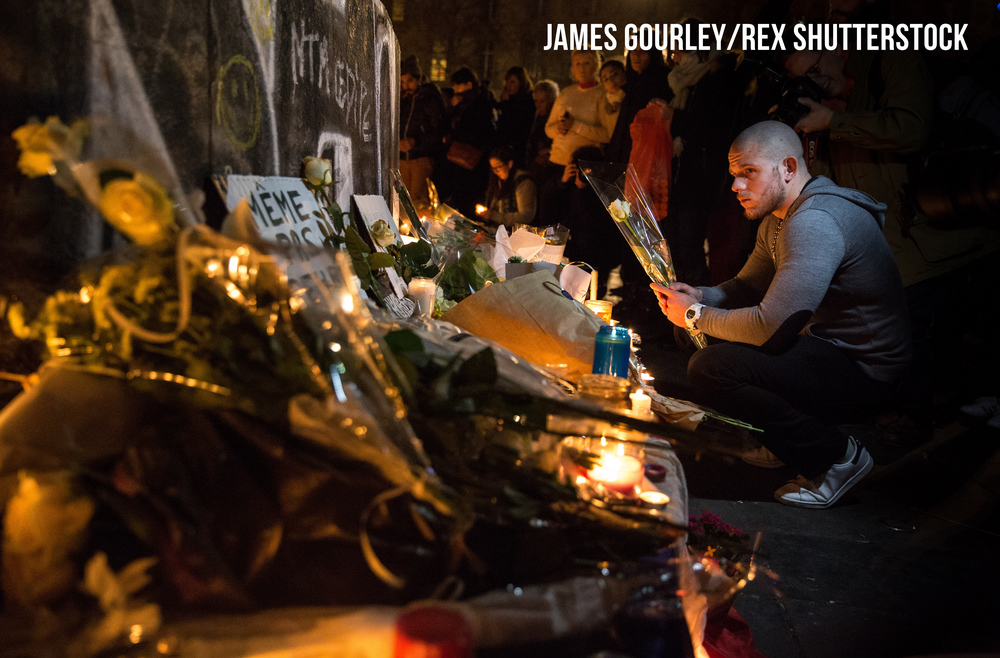 A man sits silently holding a flower at a candlelit and floral memorial to the victims at the Place de Republique