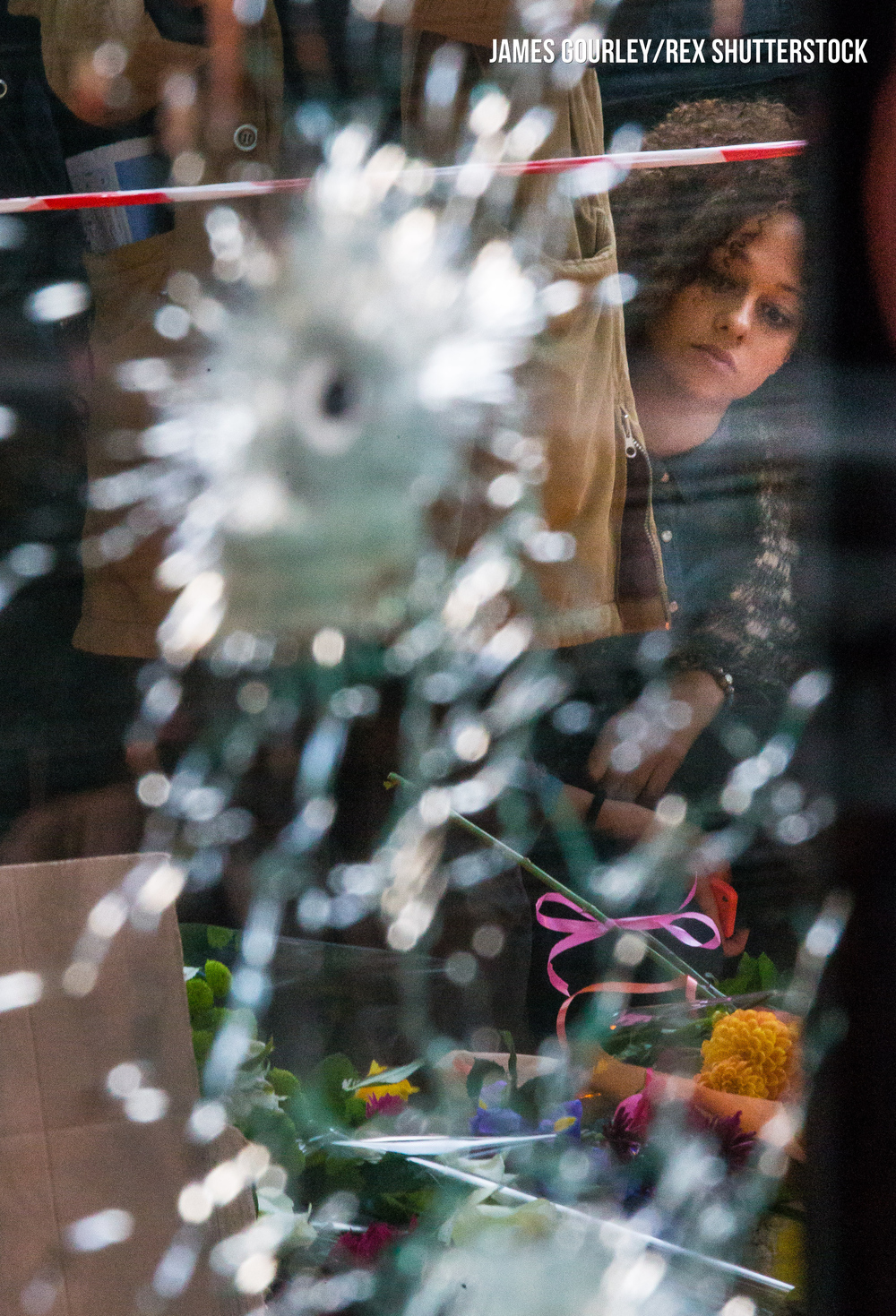 Mourners seen outside Caf� Bonne Biere through windows with bullet holes