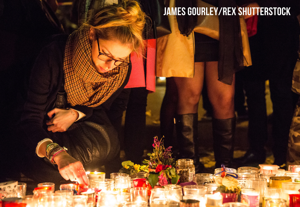 Mourners hold a vigil on the road opposite the Bataclan Café, which the Police opened this afternoon