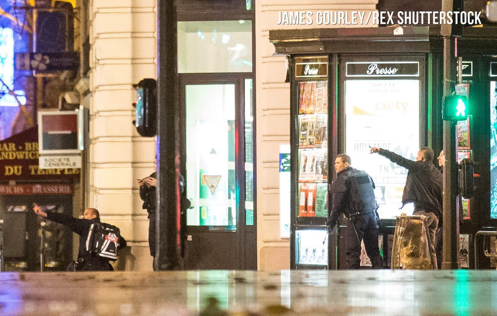 Police officers with weapons drawn in Place de Republique after an unknown scare caused thousands of people to flee the square in a panic