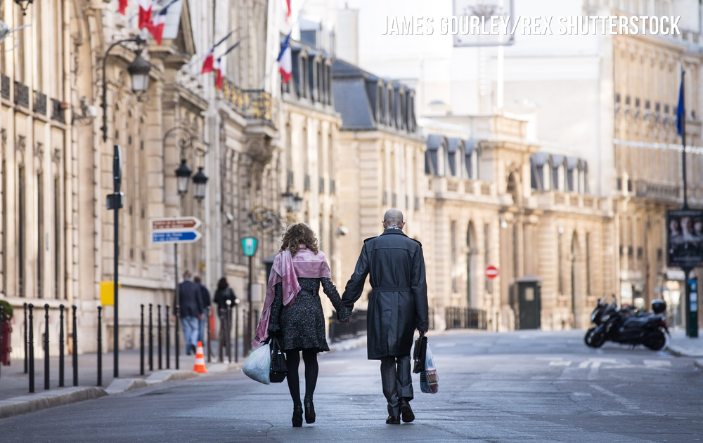 A couple walk along a nearly deserted Rue du Faubourg Saint-Honoré, which houses the Elysee palace two days after the attacks