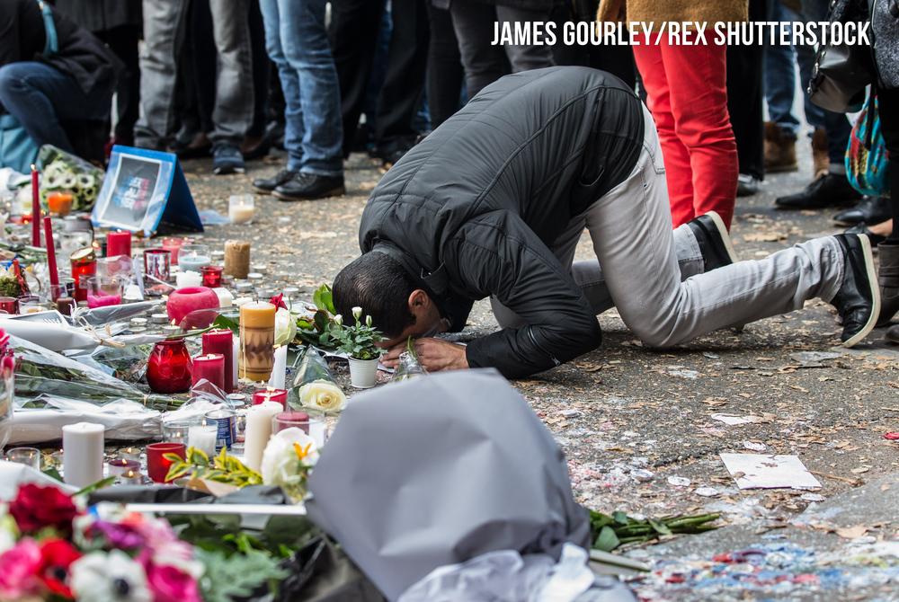 A mourner praying near the Bataclan Caf�