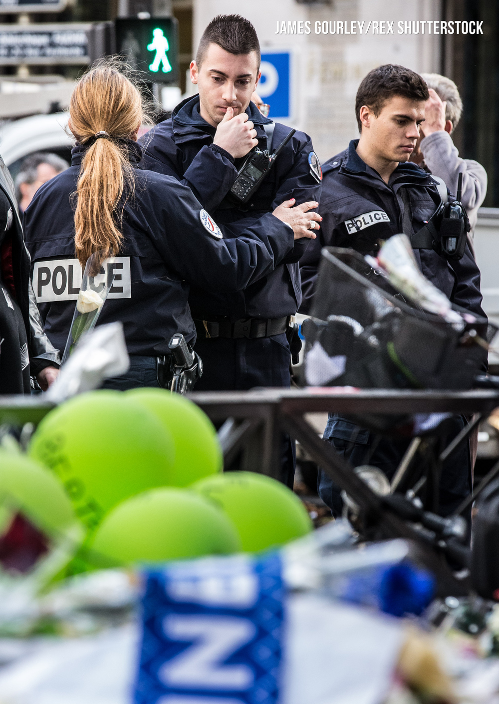 A police officer consoles a colleague at a memorial outside La Belle �quipe