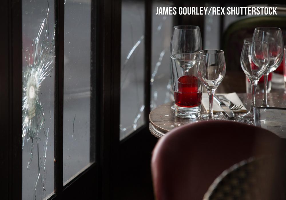 Mourners seen outside Café Bonne Biere through windows with bullet holes