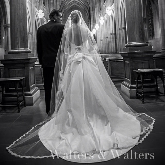 Back of a bride walking down the aisle in mantilla veil