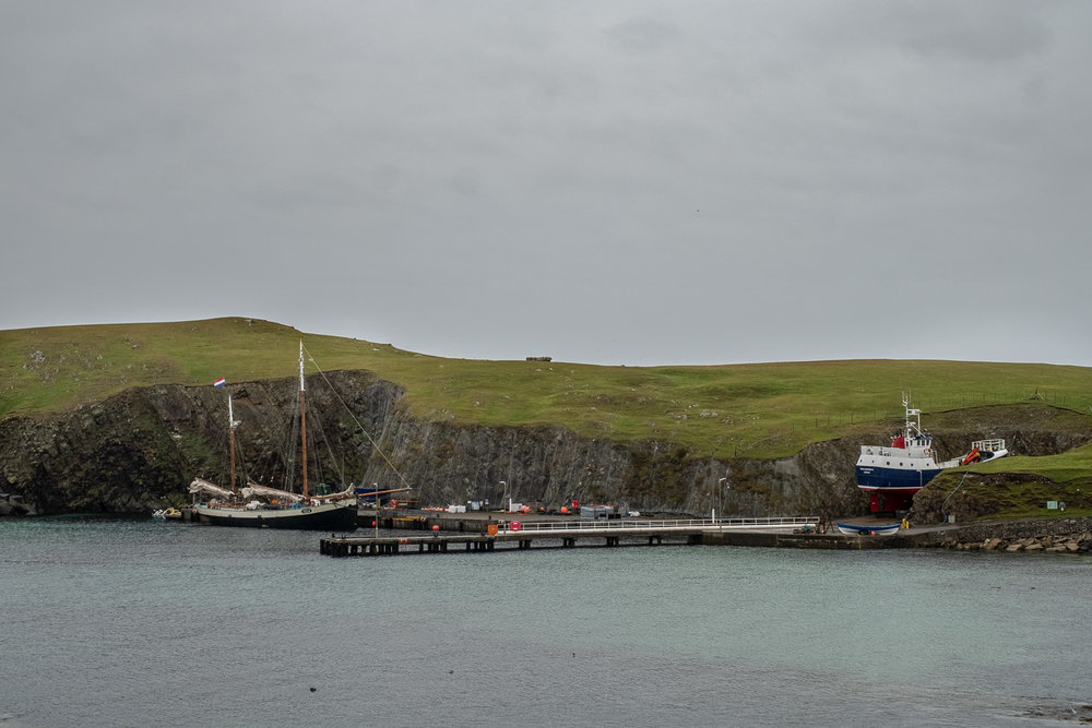 Tecla moored at the only dock on Fair Isle. Ferry in dry dock waiting to get to its mooring. Tiny black dots to the bottom left are seal heads watching our activity.