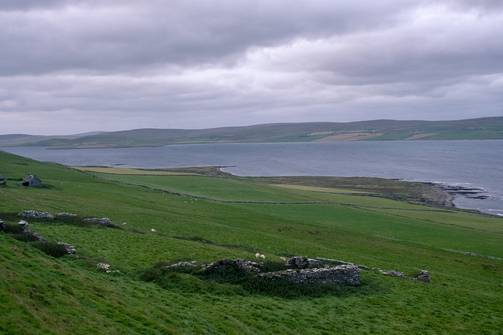 Rousay, view from 5500 year old tomb, across a ruined highland clearances home to the passage whose current wouldn't allow us to traverse it