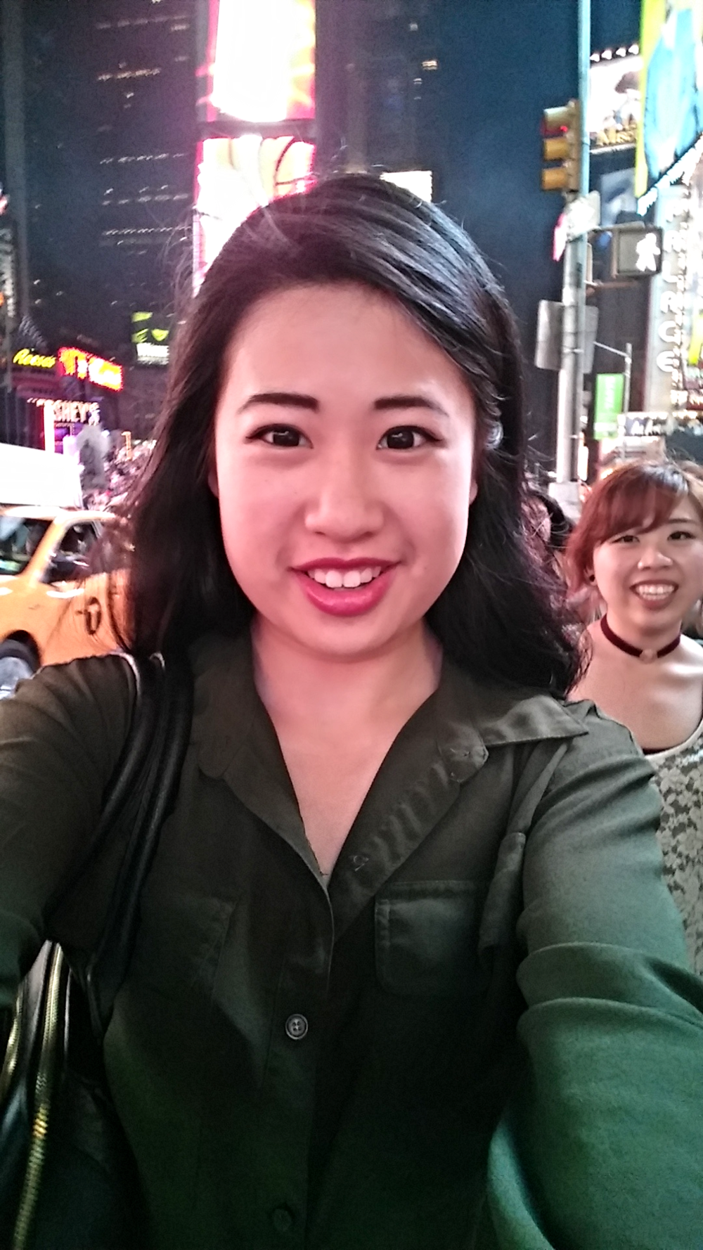 Zerlinda capturing herself in a selfie against the backdrop of the energy and craziness of Times Square in the heart of New York City.